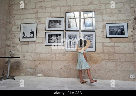 A small girl wearing two hats looks at vintage photographs in an art gallery in Arles, France. - Stock Image