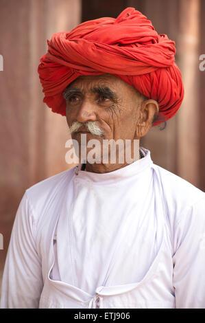 Rajasthani man in white with distinctive red turban. Rural village near Jodhpur, Rajasthan, India - Stock Image