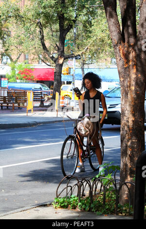 NEW YORK, NY - AUGUST 31: Young black woman in a stylish dress checks her phone while sitting on a bicycle on Bleecker Street, Manhattan on August 31, - Stock Image