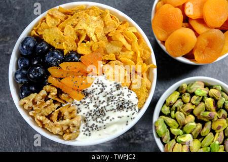 Healthy Breakfast Bowl of Corn Flakes, Yogurt, Apricots, Chia Seed, Walnuts and Fresh Blueberries - Stock Image