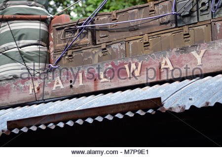 Old style wooden sign with Railway written on it. Corrugated metal roof underneath and luggage stored above. - Stock Image