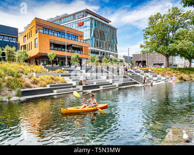 3 January 2019: Christchurch, New Zealand - A man in a kayak passes in front of The Terrace, a newly built entertainment complex on the banks of the... - Stock Image