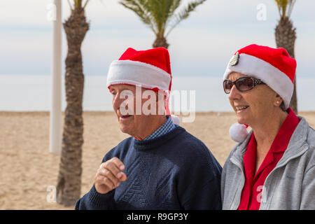 Benidorm, Costa Blanca, Spain, 25th December 2018. British tourists dress for the occasion on Christmas Day in this favourite getaway destination for Brits escaping the cold weather at home. Temperatures will be in the mid to high 20's Celsius today in this mediterranean hotspot. Couple wearing santa hats near beach. - Stock Image