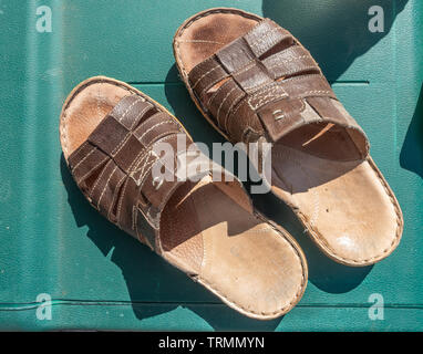 A pair of man's brown, leather sandals seen from above as worn on a summer's day. - Stock Image