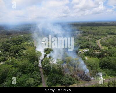 A volcanic fissure from the Kilauea volcanic eruption releases poison gases and lava as it move toward a subdivision near Leilani Street May 4, 2018 in Leilani Estates, Hawaii. The recent eruption continues destroying homes, forcing evacuations and spewing lava and poison gas on the Big Island of Hawaii. - Stock Image