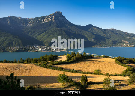 Savines-le-Lac and the Grand Morgon peak (Pic de Morgon) with Serre-Poncon Lake in morning light. Hautes-Alpes, Alps, France - Stock Image