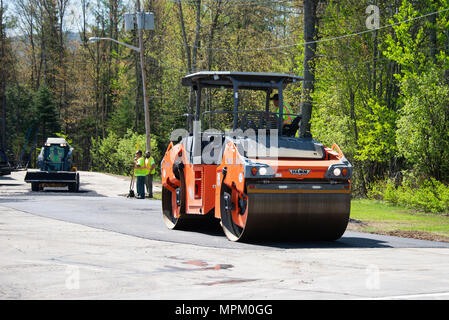 A road roller, or roller-compactor, compacting asphalt in a parking lot in Speculator, NY USA - Stock Image