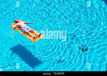 Senior aged man sleep and relax enjoying the blue water of swimming pool lay down on red watermelon lilo - summer vibes and retired lifestyle for cauc - Stock Image