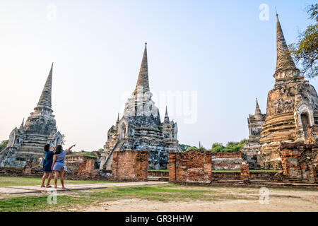 Tourists mother and daughter photography ancient ruins and pagoda of Wat Phra Si Sanphet Temple famous attractions - Stock Image