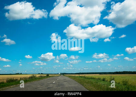 Empty asphalt road through two green field and clouds on blue sky in summer day - Stock Image