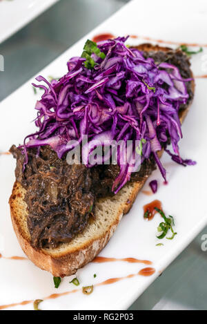 portuguese stewed beef and red cabbage toasted open sandwich tapas snack - Stock Image