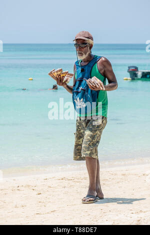 Local man in West Bay Roatan Honduras sells cigars to tourists on the beach. - Stock Image