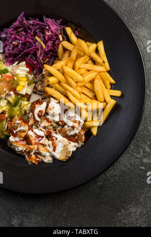 Turkish donner kebab with fries and salad on plate. - Stock Image