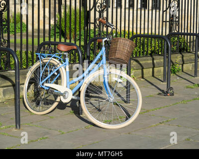 A blue ladies bicycle with an open frame rear carrier and a basket on the handle bars locked to railings - Stock Image