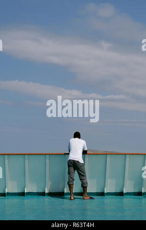 african man standing on the stern of a ship - Stock Image