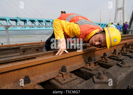 (190423) -- CHONGQING, April 23, 2019 (Xinhua) -- Tang Jinhua, a 53 year-old worker of China Railway Chengdu Group Co., Ltd., checks rails on the previous Baishatuo Yangtze River railway bridge in Jiangjin of southwest China's Chongqing Municipality, April 23, 2019. The previous Baishatuo Yangtze River railway bridge, completed in 1959, will stop service after April 24. All trains will run on the new double decker steel truss cable stay railway bridge after that day. The new bridge has 4 tracks on the upper deck for passenger trains with a designed speed of 200 kilometers per hour and 2 tracks - Stock Image