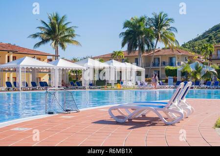 Two pool lounge chairs near a beautiful pool in Jibacoa Cuba. - Stock Image