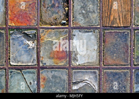 A pavement skylight; chipped, cracked and worn out from many years of heavy use. - Stock Image