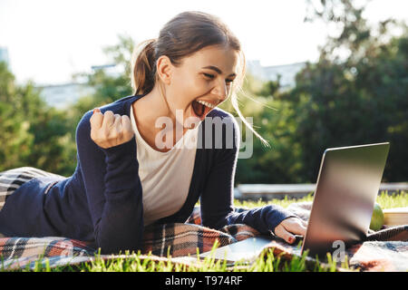 Pretty teenage girl laying on a grass at the park, studying, using laptop computer, celebrating - Stock Image