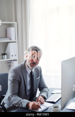Businessman with computer sitting at the table in an office, making notes. - Stock Image