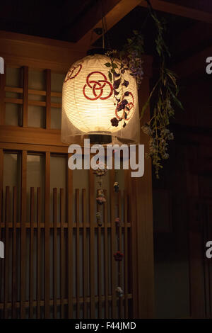 Kyoto lit lantern pattern with wooden and glass panel door behind - Stock Image