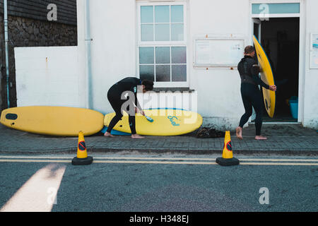 Surfer cleaning sand off yellow surfboards after a surf lesson at Sennen Cove recreation centre, Cornwall - Stock Image