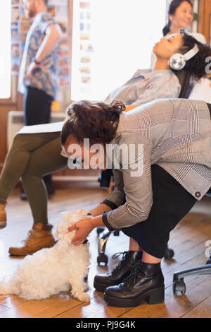 Creative businesswoman petting cute dog in office - Stock Image
