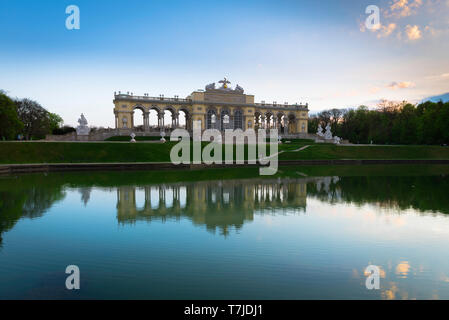 View at dusk of the Gloriette building (1775) and lake sited on a hill above the formal gardens of the Schloss Schönbrunn in Vienna, Austria. - Stock Image