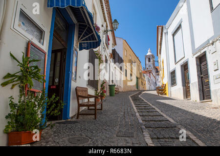 LAGOS, PORTUGAL - JULY 12TH 2018: A view up one of the streets in the historic old town of Lagos, looking towards the Church of St. Sebastian, on 12th - Stock Image