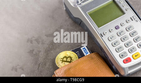 View of metal bitcoin with wallet,credit card and POS terminal.Concept image for cryptocurrency.Concept of bitcoin payment and cryptocurrency accepted - Stock Image