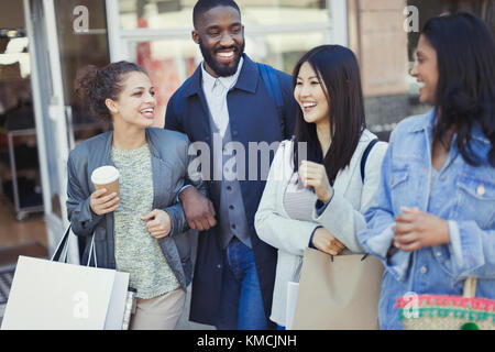 Smiling friends with coffee and shopping bags - Stock Image