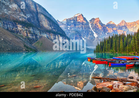 Sunrise over the Valley of the Ten Peaks with canoes on the glacier-fed, turquoise colored Moraine Lake in the Canadian Rockies. - Stock Image