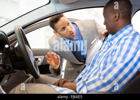 friendly salesman explaining car features to customer - Stock Image
