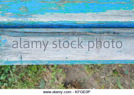 Close up of a damaged wooden bench loosing color - Stock Image