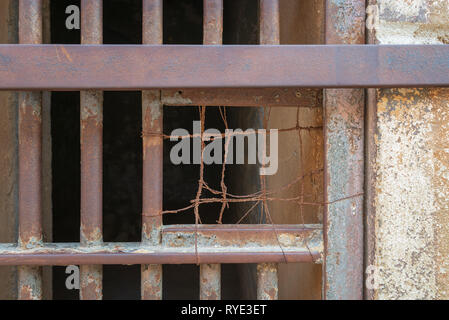 Closeup of a closed rusted iron bars of cell door in closed abandoned prison at Cairo Citadel, Egypt - Stock Image