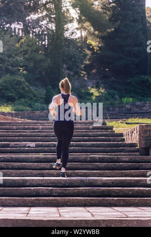 young sporty woman running upstairs in the morning on the stairs of the park, morning workout outdoors, sports and healthy lifestyle - Stock Image