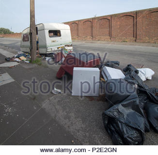 Fly-tipping of furniture and black bags by roadside, and debris spilling out of caravan abandoned in side street near Bootle Docks, Liverpool - Stock Image