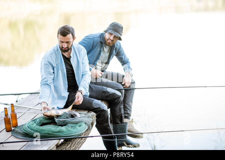 Two happy fishermen holding caught fish sitting on the wooden pier during the fishing on the lake at the morning - Stock Image