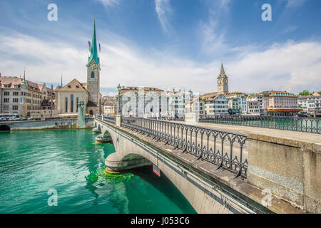 Panorama view of historic city center of Zurich with famous Fraumunster Church and Munsterbucke crossing river Limmat - Stock Image