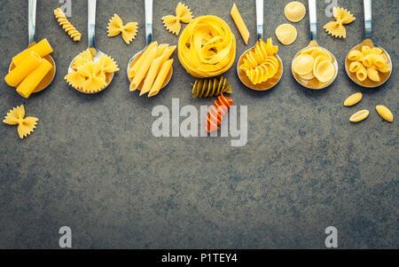 Italian foods concept and menu design. Various kind of Pasta Farfalle, Pasta A Riso, Orecchiette Pugliesi, Gnocco Sardo and Farfalle in metal spoons s - Stock Image