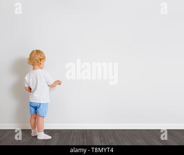 Baby boy drawing on wallpaper standing back to camera - Stock Image