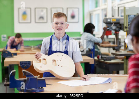 Portrait Of Male High School Student Building Guitar In Woodwork Lesson - Stock Image