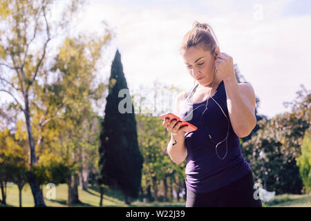 attractive blonde sports woman put on headphones before her training outdoors at park, fitness accessories - Stock Image