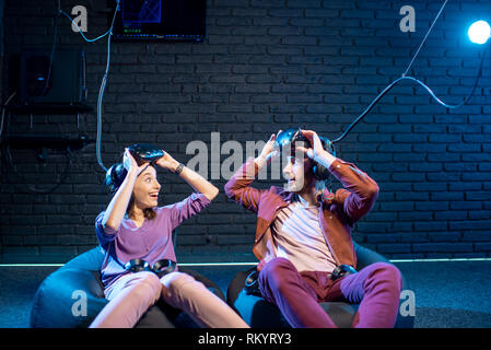 Man and woman with excited emotions sitting together after the game in virtual reality in the playing room - Stock Image