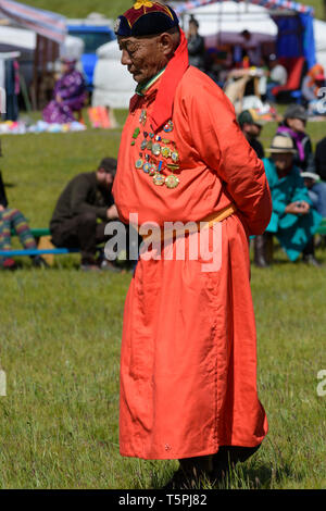 Naadam Festival in Khatgal, Mongolia. Wrestling competition. Old wrestler with many medals acting as superviser - Stock Image