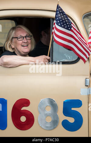 Anchorage, Alaska. 4th July, 2018. A woman waves an American flag as she rides in an classic car during the annual Independence Day parade July 4, 2018 in Anchorage, Alaska. Credit: Planetpix/Alamy Live News - Stock Image