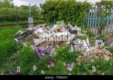 A pile of rubbish, rubble and trash from illegal fly tipping dumped beside a railway line in Nursling, Test Valley, Southampton, Hampshire, UK - Stock Image