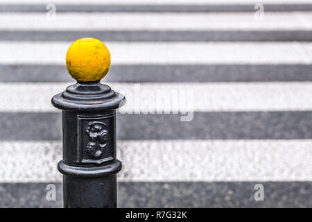 yellow metal ball on parking pole, below Warsaw coat of arms, blurred pedestrian crossing in background - Stock Image