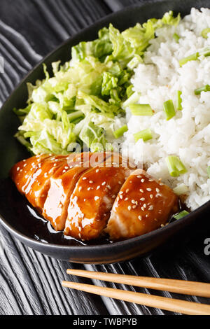 Teriyaki chicken with rice garnish and salad close-up on a plate on the table. vertical - Stock Image