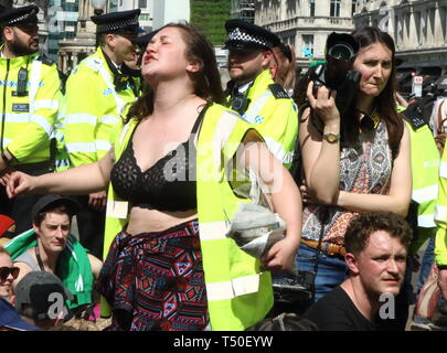 London, UK. 19th Apr, 2019. A woman seen dancing in the crowd during the demonstration.Environmental activists from Extinction Rebellion movement occupy London's Oxford Circus for a 5th day. Activists parked a pink boat in the middle of the busy Oxford Circus road junction blocking the streets and causing traffic chaos. Credit: Keith Mayhew/SOPA Images/ZUMA Wire/Alamy Live News - Stock Image